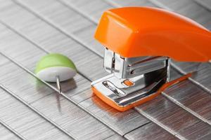 Small orange stapler on staples bed photo