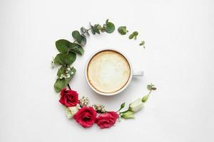 White coffee cup with fresh flowers circle at white background photo
