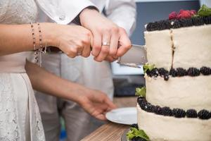 Bride and groom cut sweet cake on banquet in restaurant photo