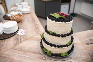 Wedding creamy cake decorated with berries on the table photo