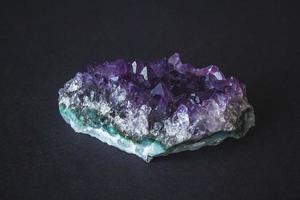 Cristales de drusa de piedra amatista sobre un fondo negro foto