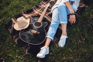 Bella mujer con guitarra descansando sobre césped verde foto