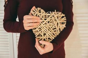 Decorative wicker heart in the hands of a woman photo