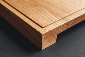 Tabla de cortar de madera artesanal sobre fondo negro foto
