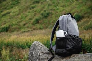 Metal cup in a backpack pocket on a nature background photo