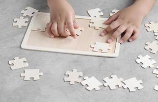 Asian little boy playing wooden jigsaw puzzle photo