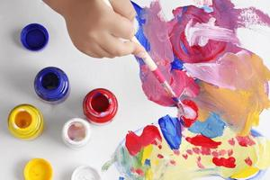 Asian boy use paintbrush and watercolor painting photo