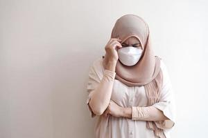Muslim wearing a surgical mask feeling sick on pastel background. photo
