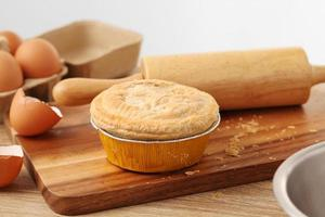 Woman hold meat pie on wooden tray photo
