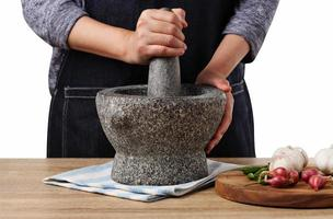Woman use stone Mortar and Pestle for cooking green curry paste photo