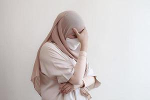Muslim woman wearing mask feeling sick on pastel background. photo