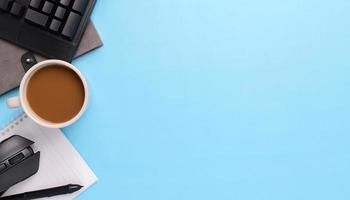 Electronic pen keyboard, mouse,notebook, coffee mug on blue background photo