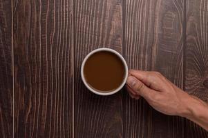Hand holding a coffee mug on a wood background photo