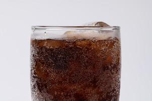 Cola en vaso con cubitos de hielo transparente aislado sobre fondo blanco. foto