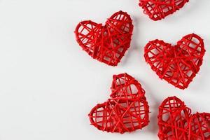 Corazones rojos hechos a mano de ramitas sobre un fondo blanco. foto