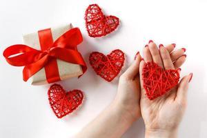 corazón rojo en las manos sobre un fondo blanco foto
