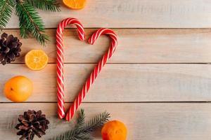 corazón de dulces navideños sobre fondo de madera. foto
