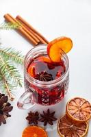Winter warming mulled wine in glass cup on white background. photo