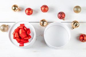 Gift boxes with red ribbon and Christmas balls on white background. photo