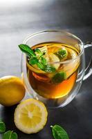 té con limón y menta en taza transparente foto