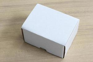 Blank paper box on wooden table background photo