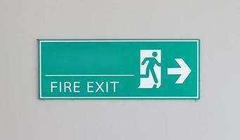 Atención señal de salida verde con flecha en la pared de fondo blanco foto