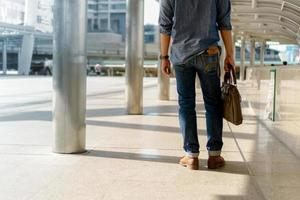Man walking in the city and holding Laptop bag photo