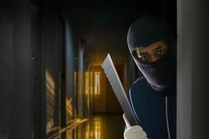 Masked robber with knife hiding behind the door photo