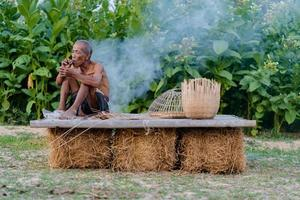 Elderly man with craft bamboo, lifestyle of the locals in thailand photo