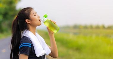 Portrait of beautiful girl in sportswear drinking water photo