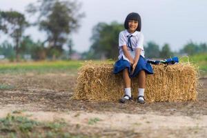 Estudiante asiático en uniforme estudiando en la campiña de Tailandia foto