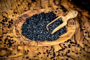 Black salt from Hawaii on olive wood photo