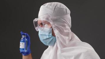 Scientist in a protective suit shows a developed vaccine against Covid. Concept of global pandemic positive end. photo