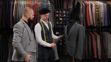 cámara lenta de hombre guapo eligiendo un diseño de traje con sastre en atelier. diseñador que presenta el traje del menequin al comprador foto