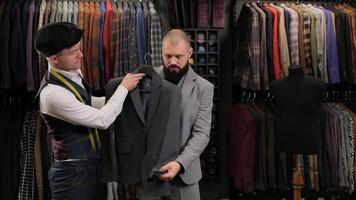 cámara lenta de hombre guapo eligiendo un diseño de traje con sastre en atelier. diseñador que presenta el blazer al comprador foto