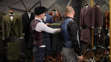 Slow motion of tailor taking a measures of handsome man for a new handmade great quality suit in atelier. photo