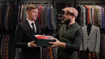 vendedor dando la caja de zapatos al cliente masculino. diseñador presentando zapatos a un hombre de negocios foto