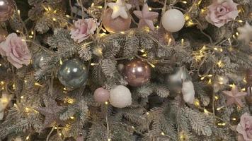 cerrar un árbol de navidad luces que brillan por la noche. abeto de año nuevo con decoración e iluminación. Fondo de decoraciones de árboles de Navidad. Muchas bolas grandes de tonos pastel en abeto año nuevo foto