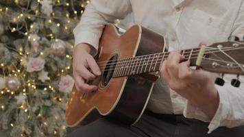 man is playing Christmas song on acoustic guitar sitting on floor near decorated New Year tree in garland lights. Happy family celebrates Christmas Eve. Close up photo