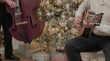 dos hombres están tocando la canción navideña con una guitarra acústica y un violonchelo cerca del árbol de año nuevo decorado con guirnaldas de luces. familia feliz celebra la víspera de Navidad. foto