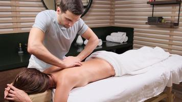 Masseur is doing massage of back of woman lying in beauty salon. Professional is massaging and touching skin of female client, using traditional techniques. photo