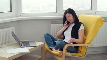 woman in casual clothes sitting on the armchair in the room, working with laptop phone and documents. distance online work at home. Brunette businesswoman doing freelance on the Internet photo