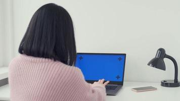 Imágenes de vista posterior de una mujer caucásica sentada frente a una computadora portátil e imprimiendo en ella. trabajo online a distancia desde casa. Morena empresaria haciendo freelance en internet foto