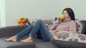 mujer en suéter disfruta de un delicioso té caliente mientras está sentada en un acogedor sofá en casa. Retrato de mujer pensativa se relaja en un sofá con una taza de delicioso café foto