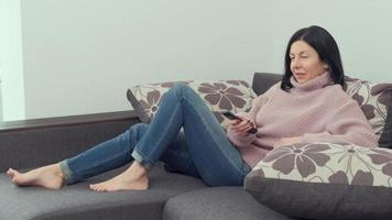 cheerful woman sitting on a sofa with a TV remote control in her hands and switching channels. photo