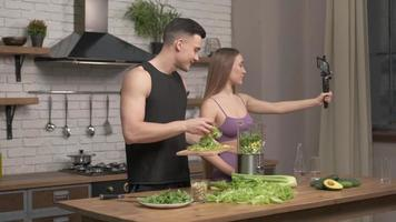 loving couple of athletes recording video food vlog about healthy cooking on phone camera in the kitchen at home. Vlogging, education and social media concept photo