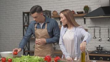 joven pareja de enamorados sonriendo, disfrutando de la preparación de comida vegetariana saludable ensalada de comida para una cena romántica en casa. foto