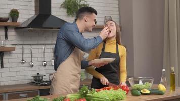 pareja de enamorados preparando comida vegetariana en la cocina de casa, marido alimenta a su amada esposa con pizza hablando y disfrutan de la cita cocinando juntos. relación romántica, concepto de plato saludable foto
