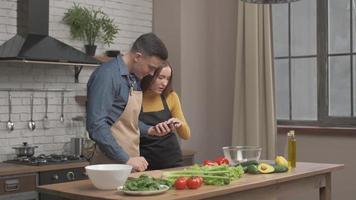 pareja mira la receta en el teléfono en la cocina para ensalada orgánica. marido y mujer cocinando comida receta. feliz estilo de vida saludable juntos. familia en busca de comida en línea. foto