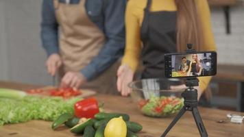 Young couple cooking together and recording video food blog on camera in the kitchen at home. focus on phone screen photo